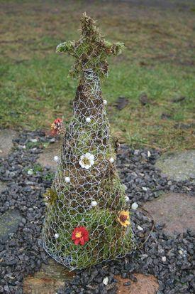 Juletræ med stjerne lavet af trådnet og fyldt op med mos og kogler