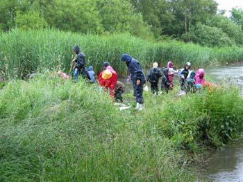 Børn i regntøj ved en sø