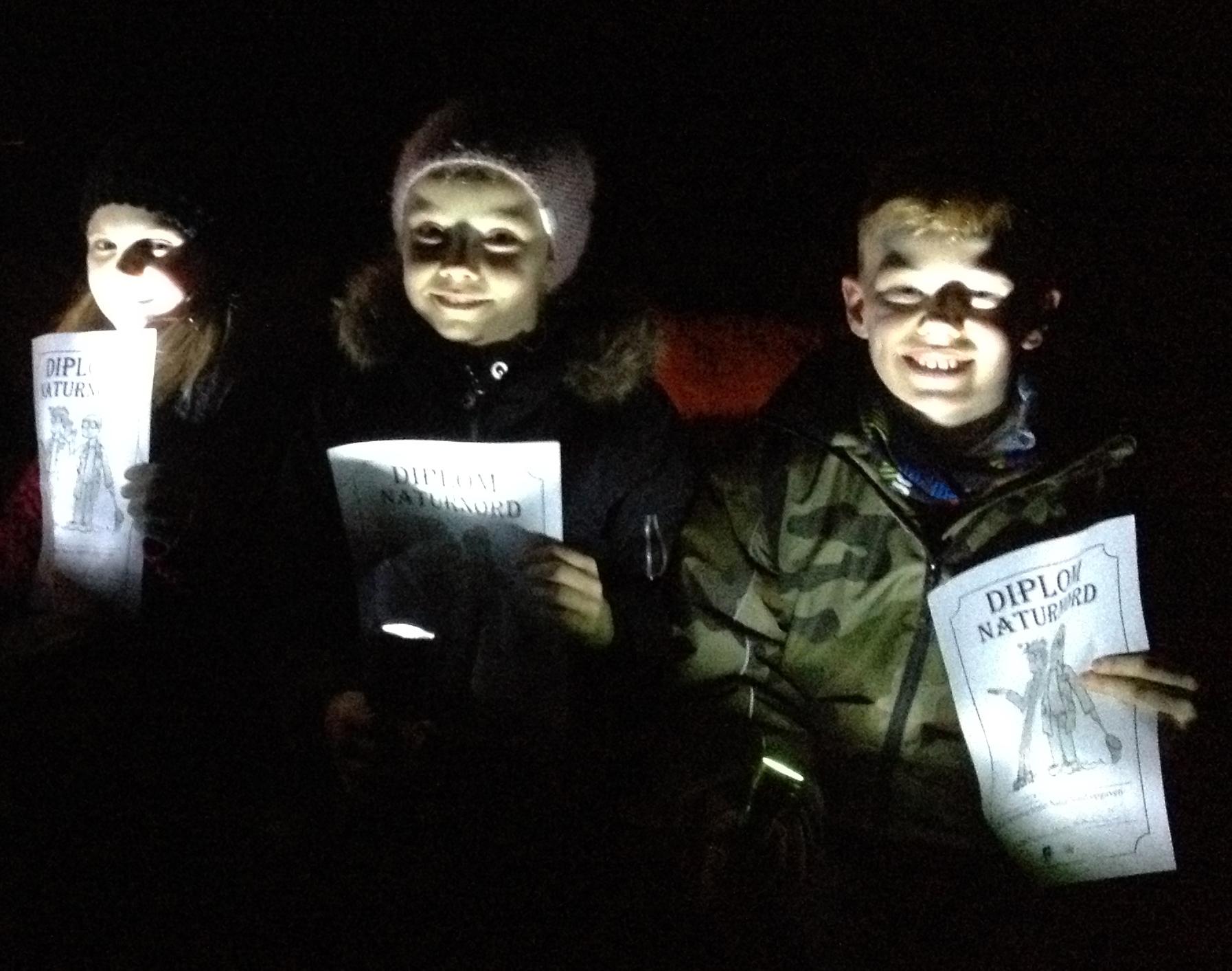 Børn i skoven lyser med lommelygter og viser deres Naturnørd diplom