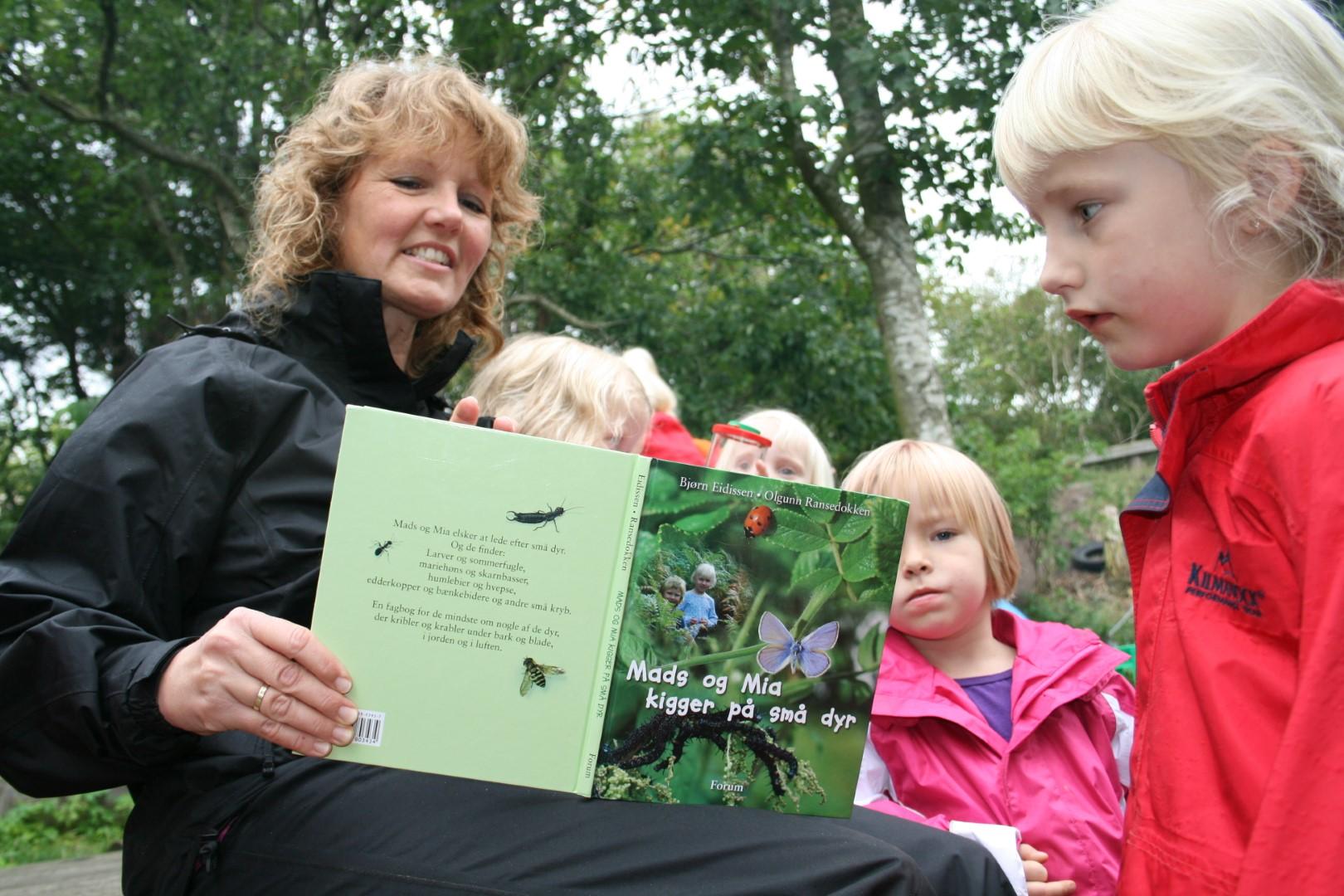 Billede af pædagog som læser højt fra en bog ude i naturen