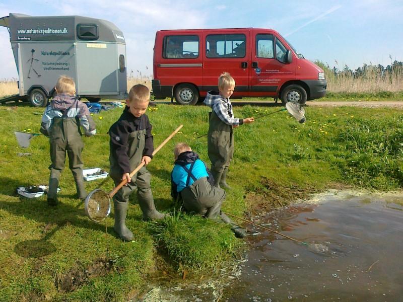 Fire drenge som fisker med net