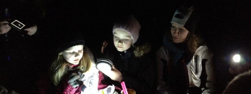 børn lyser med lommelygte på et kort