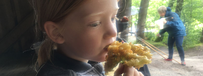 Pige som smager på en friturebagt hyldeblomst
